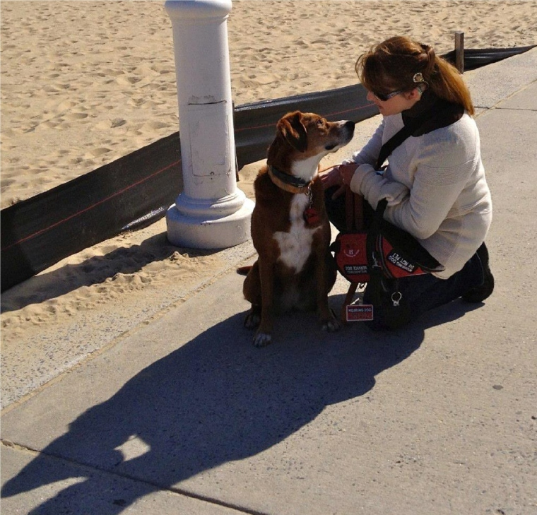 At the beach in Ocean City with cochlear implant, hearing aid, and hearing assistance dog